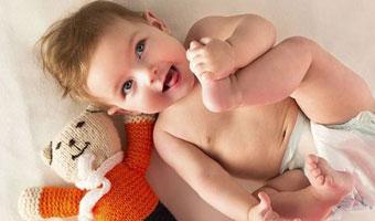 Bébé allongé sur le dos, attrape son pied