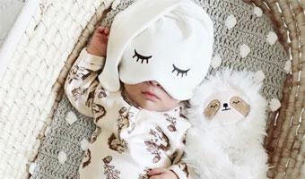 Bébé dort dans un couffin avec un bonnet rigolo