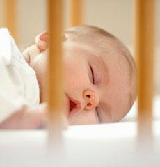 Bébé dort dans lit à barreaux