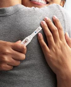 Couple se caline avec test de grossesse