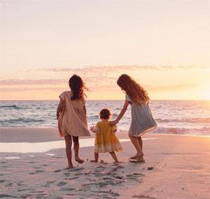 Deux fillettes et un bébé de dos sur la plage