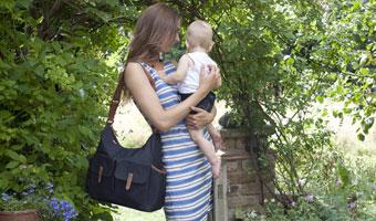 Maman avec sac à langer à l'épaule et son bébé dans les bras