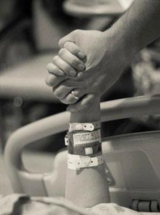 A la maternité, maman tient la main de son bébé