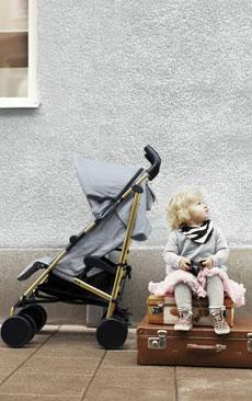 Petite fille assise à côté de sa poussette